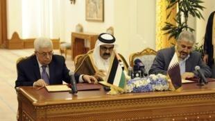 Палестинский президент, глава Фатх Махмуд Аббас (слева) и лидер Хамаса Халед Машаль (справа) в присутствии эмира Катара подписывают соглашение в Дохе 6 февраля 2012 г.