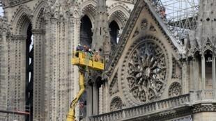 Operários trabalham na proteção do prédio da catedral, nesta segunda-feira (29)