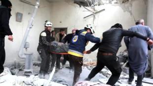 Socorristas transportan a un herido después de un bombardeo de las fuerzas gubernamentales, el 26 de febrero 2019, en Khan Sheikhoun, provincia de Idlib.