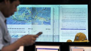 Un agent du gouvernement indonésien contrôle la réception d'un SMS d'alerte au tsunami, à Jakarta, le 9 septembre 2014.