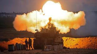 Israeli soldiers fire towards the Gaza Strip from their position along the border with the Palestinian enclave