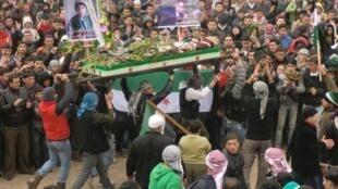 Manifestantes contra o governo de Bashar al-Assad em funeral de rebelde morto pelas tropas do goverbo na região de Idlib.
