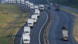 Une longue file de camions blancs, des dizaines de véhicules, s'achemine vers la frontière ukrainienne, en direction de Lougansk, ville contrôlée par les séparatistes pro-russes.