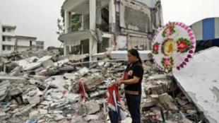 2008年5月20日,四川省都江堰地震灾区,一位妇女手拿运动服站在聚源一所倒塌的学校