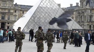 Quelques touristes attendent  l'ouverture du musée du Louvre, haut lieu culturel et touristique de la capitale, sous haut surveillance.