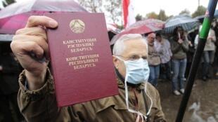 Un homme brandit le Code constitutionnel pendant la manifestation, à Minsk, le 8 octobre 2011.