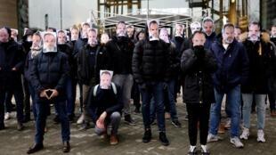 Des salariés de Canal+ arborant le masque à l'effigie de Stéphane Guy, licéncié par sa direction, manifestent devant le siège du groupe à Boulogne-Billancourt, le 5 janvier 2021
