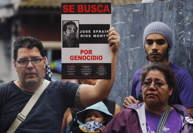 A Guatemala City, cet homme brandit une affiche sur laquelle on peut lire: «Rios Montt recherché pour génocide».