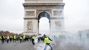 Tear gas floats in the air near the Arc de Triomphe as protesters demonstrate against fuel taxes.