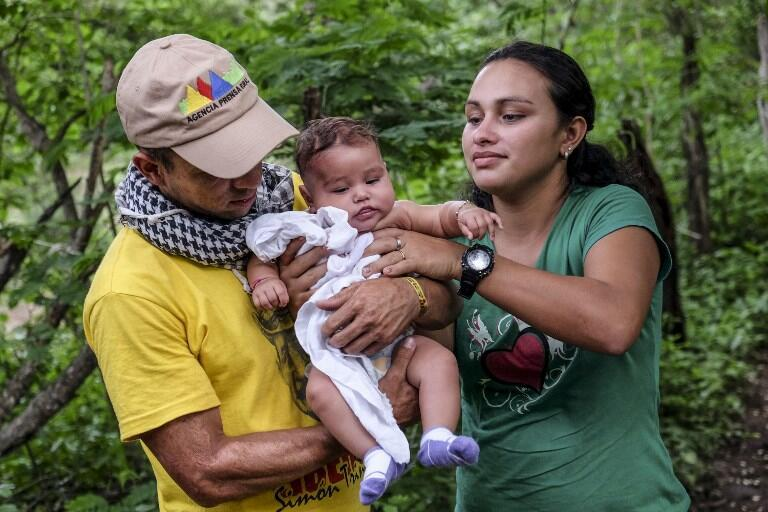 A Farc guerrilla couple takes care of a baby at their camp in Pondores, La Guajira department, Colombia on 3 April, 2017