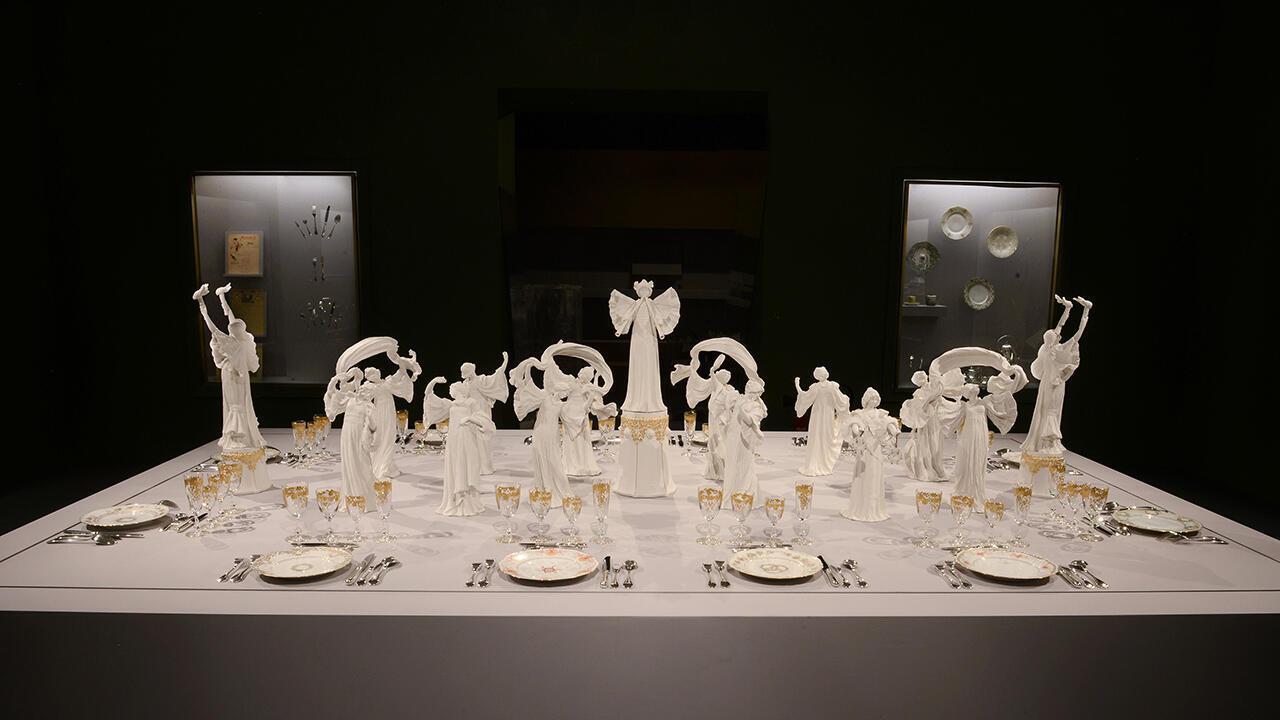 Стол, повторяющий сервировку в Елисейском дворце 1900 г. Сюрту «Танец с шарфом» Агатона Леонарда, тарелки из различных сервизов севрской мануфактуры, хрусталь Saint-Louis, серебро Christofle