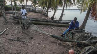 Lamine Sagna (g.), pêcheur de crevettes, vit sur la bande de terre de Grand Lahou, en Côte d'Ivoire. Il a dû déménager sa maison plusieurs fois pour fuir l'océan qui gagne chaque année plus de terrain.