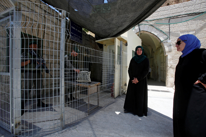 在希伯伦的以色列始祖亚伯拉罕坟墓前,该国警察护栏内正检查两名前往祈祷的妇女 。  2017年6月16日