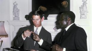 Robert Mugabe, wakati huo alikuwa Waziri Mkuu wa taifa jipya la Zimbabwe(zamani ikiitwa Rhodesia), akikabidhi medali ya uhuru kwa mwanamfalme Charles, Aprili 1980.