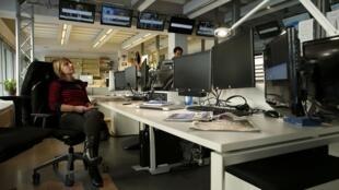 Des employés de la chaîne française TV5Monde sont assis devant leurs écrans noirs, après la cyber-attaque dont elle a été la cible le mercredi 8 avril.