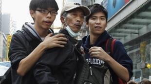 2014年11月26日,香港警方在旺角占领区清场时,学民思潮召集人黄之锋(左)与专上学联副秘书长岑敖晖(右)将一名示威者拉回到路障后。