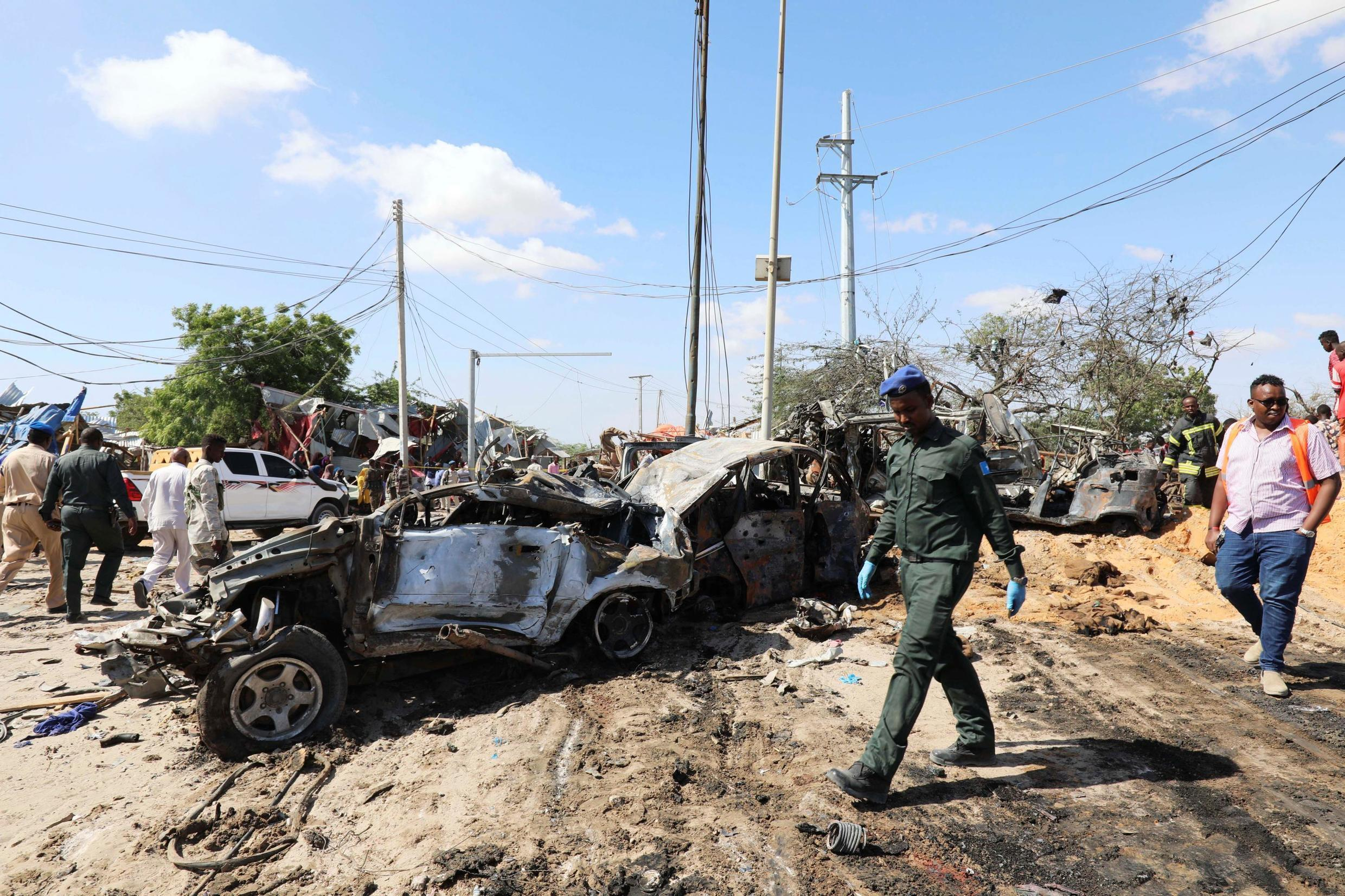 A Somali police officer walks past a wreckage at the scene of a car bomb explosion at a checkpoint in Mogadishu,28 December, 2019.