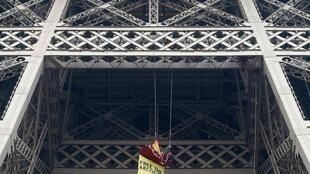 A Greenpeace activist hangs from the Eiffel Tower in a stunt in solidarity with the 30 jailed in Russia