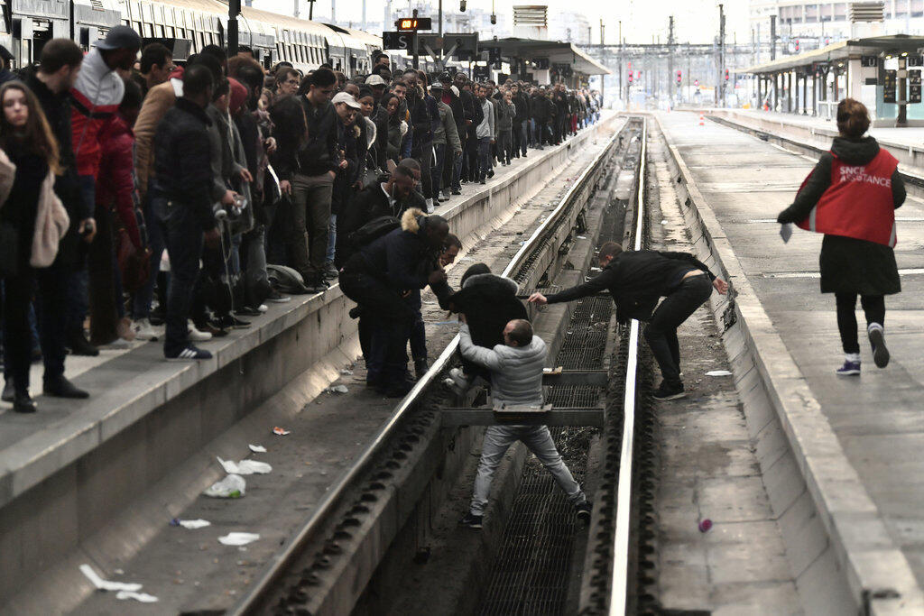 People help a woman who fell onto a railtrack in Gare de Lyon railway station in Paris on April 3, 2018, at the start of three months of rolling rail strikes. Staff at state rail operator SNCF walked off the job from 7.00 pm (1700 GMT) on April 2.