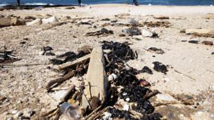 Des amas de goudron après un déversement de pétrole en mer qui a inondé une grande partie du littoral méditerranéen sur une plage d'Ashdod, dans le sud d'Israël, le 21 février 2021.