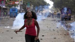Une femme s'enfuit après avoir jeté des pierres sur la police lors d'une émeute à Eastleigh, au Kenya, le 19 Novembre, 2012.