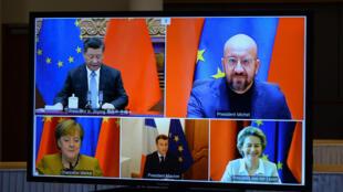 De arriba abajo y de izquierda a derecha, Xi Jinping, Charles Michel, Angela Merkel, Emmanuel Macron y Ursula von der Leyen, durante su reunión por videoconferencia, en una pantalla el 30 de diciembre de 2020 en Bruselas