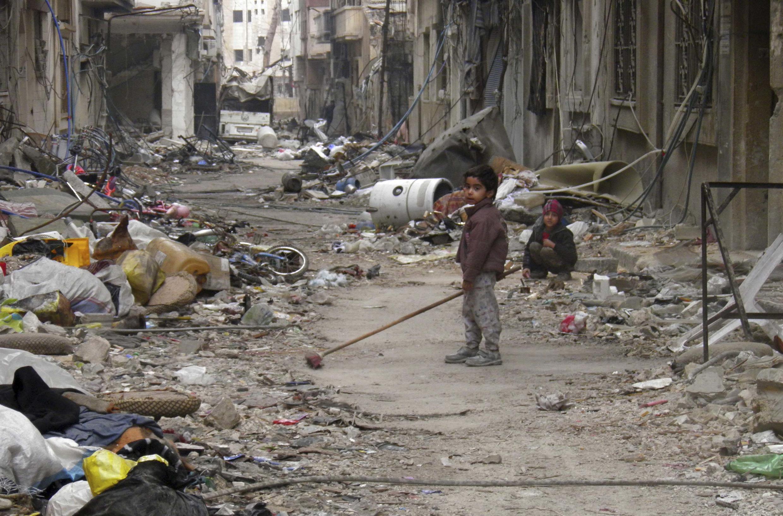 Niños en medio de escombros.