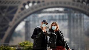 Des touristes se prennent en photo devant la Tour Eiffel le 20 mars 2020.
