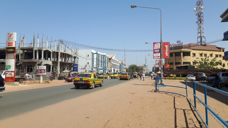 NAWEC, compagnie nationale d'eau et d'électricité qui fournit tout le pays, croule sous les dettes. Résultat : les coupures de courant sont presque quotidiennes dans certains quartiers.<br>Photo: Kairaba avenue, principale artère de Banjul<br>