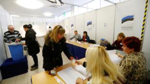 Un agent électoral inspecte une pièce d'identité dans un bureau de vote de Parnu, pour les élections générales en Estonie, le 3 mars 2019.
