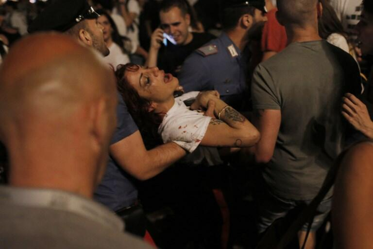 Torcedor ferido é carregado na praça San carlo, em Turim.