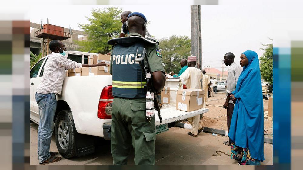 Un membre de la police supervise le personnel ad hoc chargeant des boîtes dans un camion lors de la distribution de matériel électoral au bureau de l'INEC à Yola, dans l'État d'Adamawa, au Nigéria, le 15 février 2019.