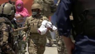 Wani sojan Afghanistan bayan ceto daya daga cikin jariran da harin 'yan ta'adda ya rutsa da su a babban asibitin Kabul, babban birnin Afghanistan. 12/05/2020.