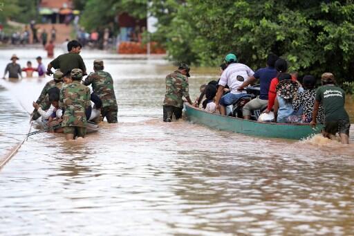 Soldados cambojanos evacuam os moradores de barco das enchentes na província de Stung Treng em 26 de julho de 2018.