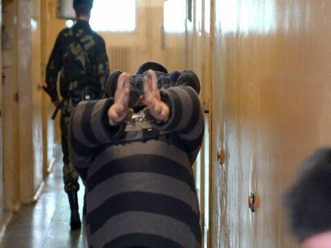 Осужденного к смертной казни заставляют ходить с опущенной к коленям головой и с высоко поднятыми за спиной руками в наручниках. На фото: доставка заключенных в Жодинской тюрьме No8. Источник: ПЦ «Весна»