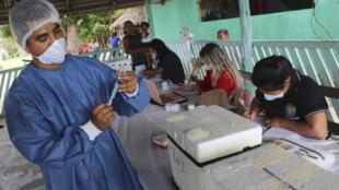 Un agende de salud llega preparando una inyección de la vacuna Sinovac durante una campaña de vacunación COVID-19 para puebos originarios prioritarios, en la aldea Nova Esperança, en las afueras de Manaos, Brasil, el miércoles 17 de marzo de 2021