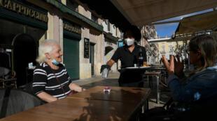 Una camarera le sirve un café a unas clientas en la ciudad española de Tarragona el 11 de mayo de 2020, cuando algunas regiones españolas iniciaron el desconfinamiento
