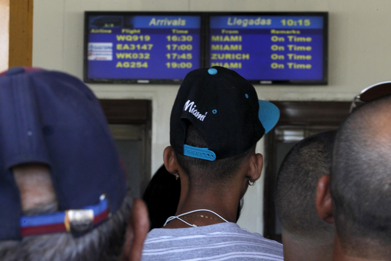 Cubanos esperam diante do terminal de desembarque do aeroporto de Havana, onde número de chegadas de turistas vem aumentando no último ano.