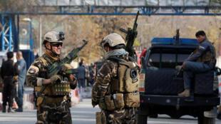 Des membres des forces de sécurité montent la garde et examinent le site d'une explosion kamikaze à Kaboul, le 12 novembre 2018.