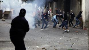 Un policía antidisturbios lanza gases lacrimógenos contra un grupo de manifestantes en el barrio de Belcourd, Argel, 7 de enero de 2011.