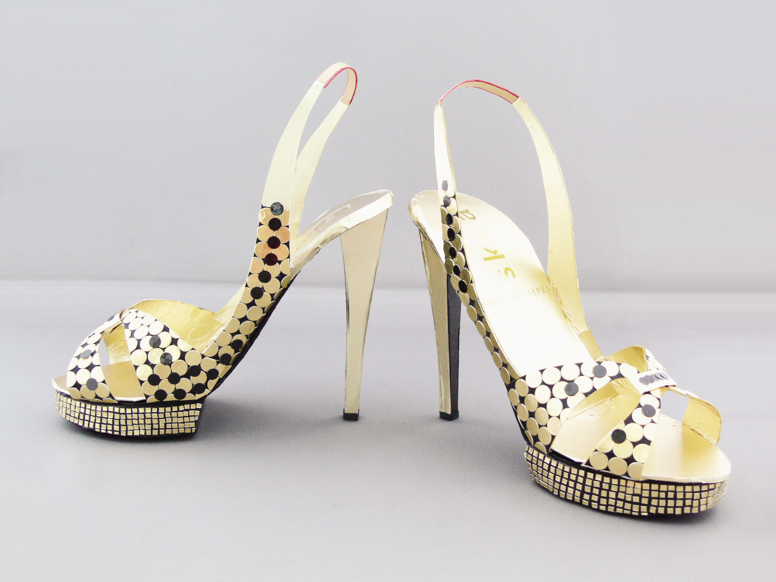 These shoes are made of paper, and are a funeral offering, meant to accompany the defunt into the after life. They will be burnt after the funeral.