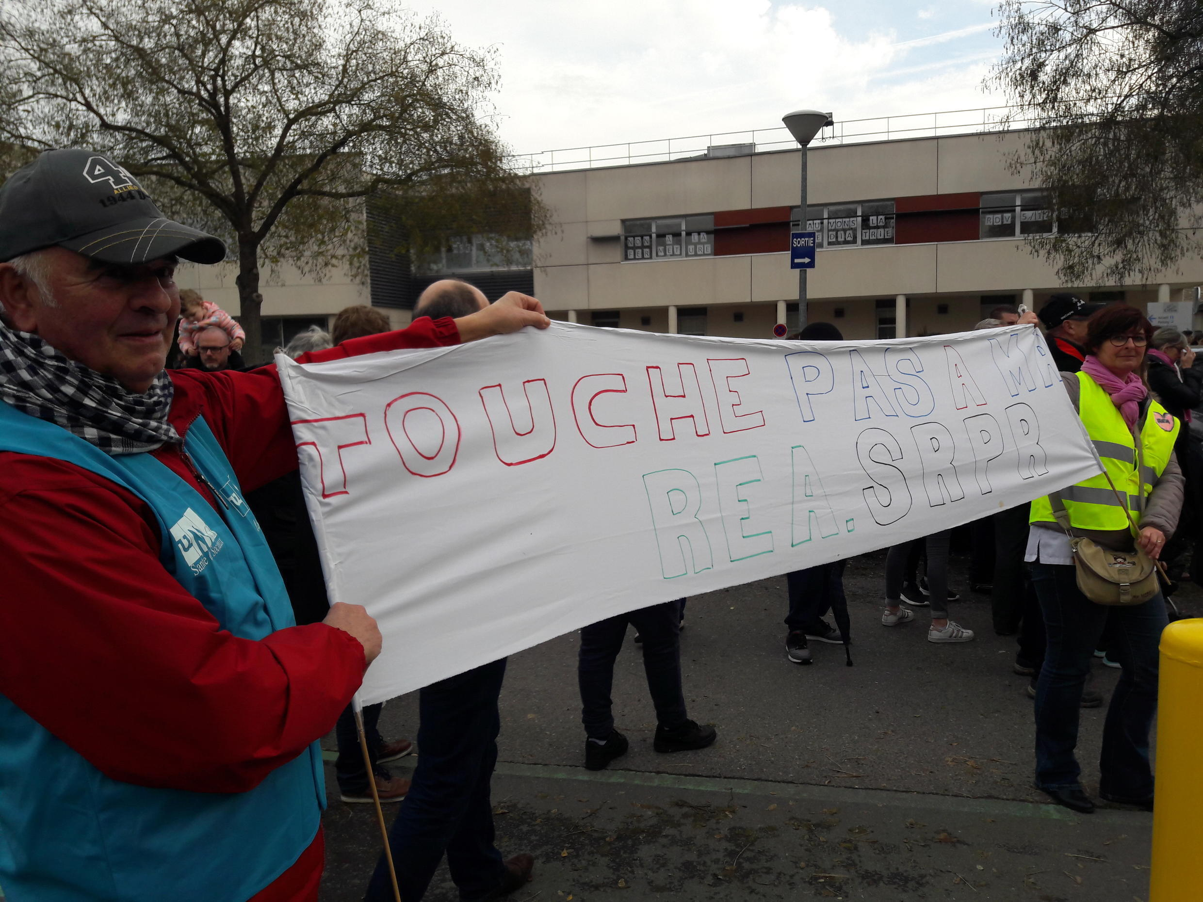 A Yellow Vest protester and a trade unionist hold a banner calling to save the hospital, December 5 2018.