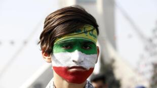 Un jeune Iranien au visage peint aux couleurs du drapeau iranien, dans la foule venue écouter le président Rohani, à Téhéran, le 11 février 2018.
