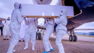 Des hommes portant un équipement de protection portent le cercueil du chef de cabinet du président nigérian, Abba Kyari, décédé vendredi après avoir contracté la maladie à coronavirus (Covid-19). Nigeria, le 18 avril 2020.