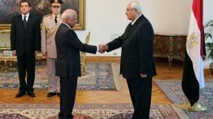 Poignée de main entre le président par intérim Adly Mansour (d.) et le nouveau Premier ministre Hazem el-Beblaoui, le 16 juillet 2013 au Caire.