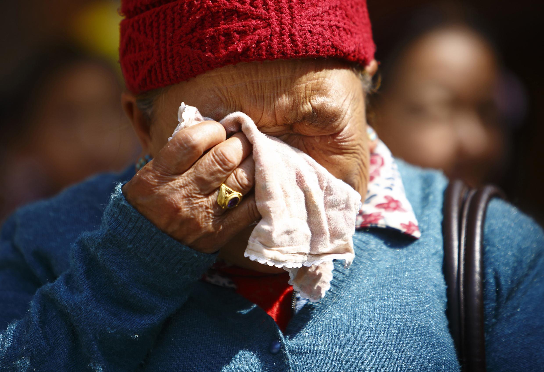 Mãe de um dos guias mortos chora em frente a necrotério.