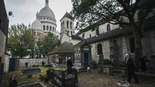 Visitors walk inside the Calvaire cemetery, Paris' smallest cemetery, near the Sacre-Cœur Basilica (background) in Paris on November 1, 2018, on the All Saints' Day.