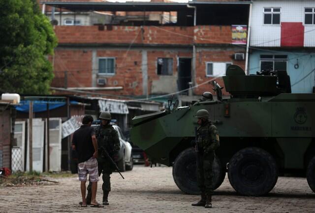 Soldados do Exército controlam documentos de morador da favela Kelson's, na Penha, no Rio de Janeiro.