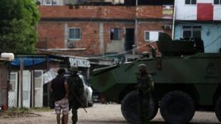 Des soldats de l'armée contrôlent les documents d'un habitant de la favela Kelson's, le 20 février 2018 à Rio de Janeiro.