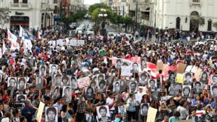 Durante protesto, manifestantes exibiram fotos de vítimas assassinadas por esquadrões da morte do Exército peruano durante o regime de Fujimori.
